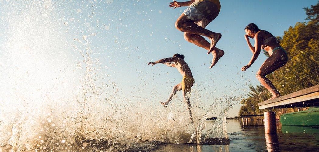 Friends having fun enjoying a summer day swimming and jumping at